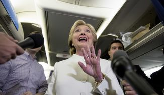 Democratic presidential candidate Hillary Clinton, center, accompanied by Campaign Manager Robby Mook, left, and traveling press secretary Nick Merrill, right, waves after speaking with members of the media aboard her campaign plane at McCarran International Airport in Las Vegas, Wednesday, Oct. 19, 2016, following the third presidential debate. (AP Photo/Andrew Harnik)