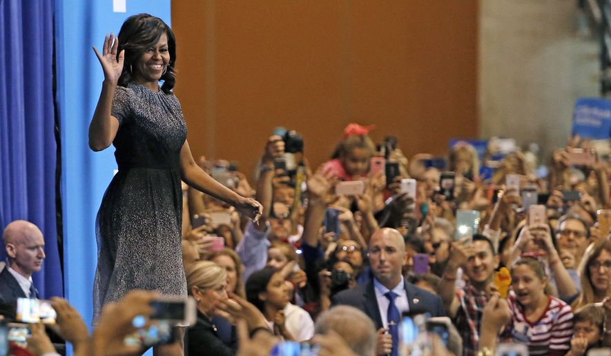 First lady Michelle Obama waves to supporters as she arrives on stage prior to speaking during a campaign rally for Democratic presidential candidate Hillary Clinton Thursday, Oct. 20, 2016, in Phoenix. (AP Photo/Ross D. Franklin)