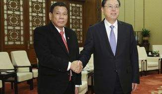 Philippines President Rodrigo Duterte, left, poses with Zhang Dejiang, chairman of the Standing Committee of the National People's Congress of China, prior to a meeting at the Great Hall of the Peopleat the Great Hall of the People in Beijing Thursday, Oct. 20, 2016. China and the Philippines have agreed to resume a dialogue on their dispute over the South China Sea, a senior Chinese diplomat said Thursday following talks between the countries' leaders. (Wu Hong/Pool Photo via AP)