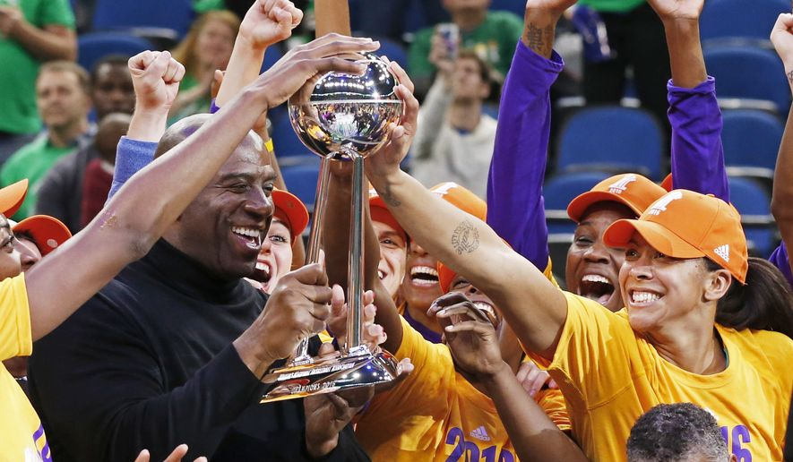 Los Angeles Sparks' Candace Parker, right, touches the trophy held by team owner Magic Johnson after the Sparks won the WNBA championship title with a win over the Minnesota Lynx in Game 5, Thursday, Oct. 20, 2016, in Minneapolis. (AP Photo/Jim Mone) **FILE**