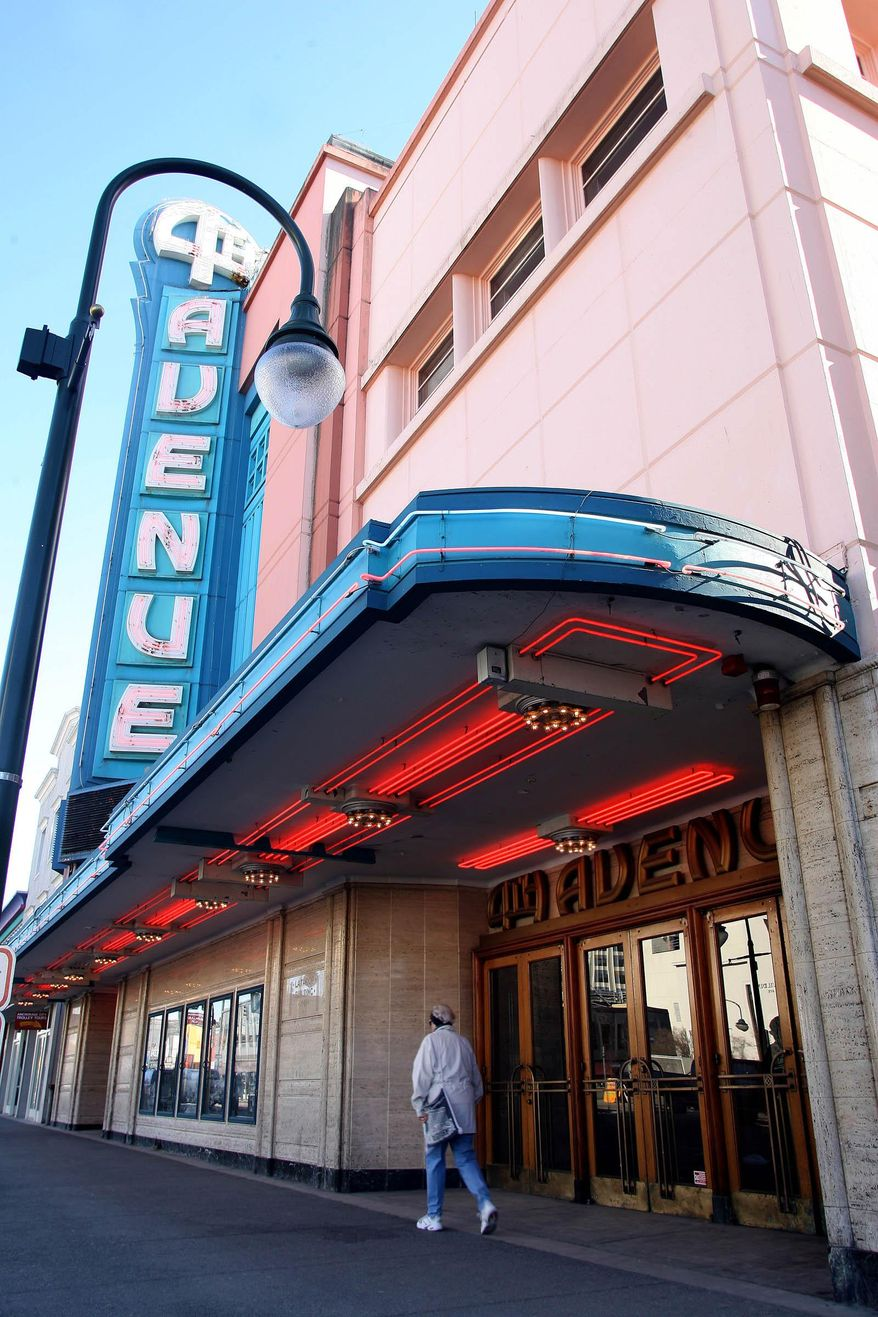 FILE - In this March 29, 2006, photo, a pedestrian walks past the 4th Avenue Theatre in Anchorage, Alaska. The owners of the art moderne-style theater, designed by the architect of Hollywood's famed Pantages Theatre, have applied to demolish the opulent vintage icon, prompting the Municipality of Anchorage to hasten efforts to protect historic buildings. (AP Photo/Al Grillo, File)