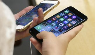 In this Sept. 16, 2016, file photo, Lisa Gao, from Chicago, compares a new jet black iPhone 7, right, with her iPhone 6 at an Apple Store in Chicago. (AP Photo/Kiichiro Sato, File)