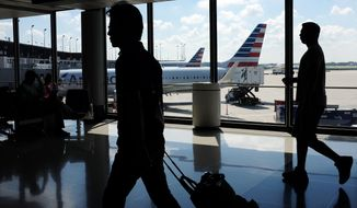 In this Monday, Aug. 1, 2016, photo, passengers walk to their gates through the terminal as American Airlines planes wait to depart at O'Hare International Airport in Chicago. American Airlines reports financial results Thursday, Oct. 20. (AP Photo/Kiichiro Sato)
