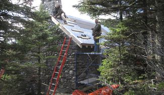 In this Wednesday, Oct. 19, 2016 photo workers rebuild an historic stone cabin on Mount Mansfield in Stowe, Vt. The building was gutted in a fire last Christmas Eve when the founder of Burton Snowboards' two sons accidentally caused a fire. The family donated $150,000 to help rebuild the Stone Hut, which will be open for overnight guests starting on Dec. 1. (AP Photo/Lisa Rathke)