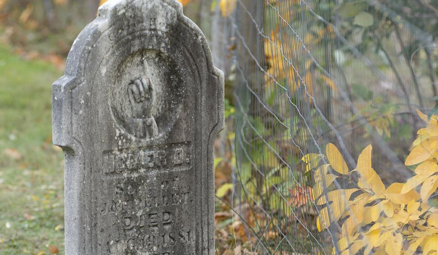 A grave from the late 1800s sits very close to the edge of Wildwood Cemetery, in Chesaning Township, Mich., on Oct. 18, 2016. Portions of the township's Wildwood Cemetery are collapsing into the Shiawassee River due to erosion. This has prompted township officials to start the process of attempting to contact relatives of those buried along the riverbank, so that the bodies may be exhumed and moved to a different part of the cemetery. Some of the graves are more than 100 years old. (Jeff Schrier/The Saginaw News-MLive.com via AP)