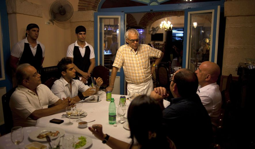 FILE - In this July 11, 2012 file photo, Tomas Erasmo Hernandez, center, owner of the private restaurant Mama Ines, chats with his customers in Old Havana, Cuba. Cuba is temporarily freezing new licenses for private restaurants in Havana, announced by acting Vice President Isabel Hamze on state media on Wednesday, Oct. 19, 2016. The city is also starting to impose more limits on private bed-and-breakfasts. (AP Photo/Ramon Espinosa, File)