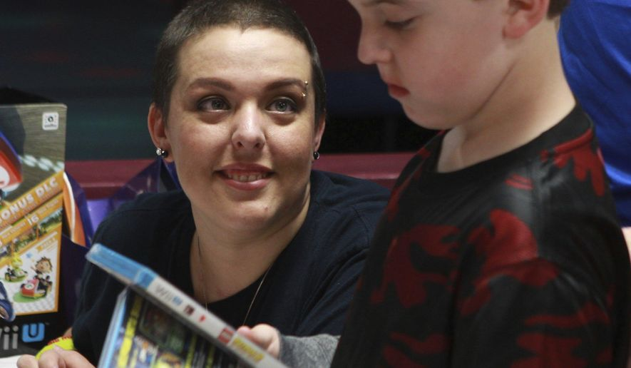ADVANCE FOR SUNDAY OCT. 23 AND THEREAFTER - In an Oct. 3, 2015 photo, Jennifer Cooper, 34, looks at her son Devon during his 8th birthday party at Angelo Skate and Fun Center. Cooper has metastatic breast cancer and is now on in-home hospice care. Since her diagnosis, Jennifer Cooper has counted time by birthdays and holidays. (Michelle Gaitan/Standard-Times via AP)