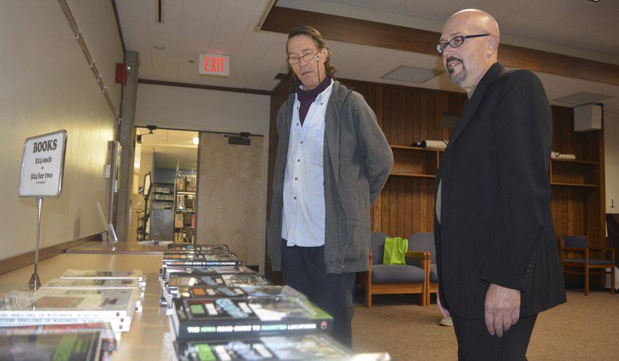 ADVANCE FOR USE SATURDAY, OCT. 22, 2016 AND THEREAFTER - In this  Oct. 9, 2016 photo, William Gustavson of Bloomington, left, talks with author and featured lecturer Terry Fisk prior to a program at the Bloomington Public Library in Bloomington, Ill. Fisk a cryptozoologist, discussed monsters and creatures that have become a part of folklore throughout Central Illinois. (Kevin Barlow/The Pantagraph via AP)