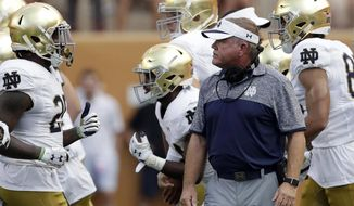 FILE - In this Sunday, Sept. 4, 2016, file photo, Notre Dame head coach Brian Kelly, center, watches as his players run off the field during the first half of an NCAA college football game against Texas in Austin, Texas. Simpler and louder have meant better so far at Texas and Notre Dame, with both head coaches taking more hands-on roles to fix bad defenses after replacing coordinators. The two traditional powers are showing improvement after making changes at defensive coordinator, although both are stills works in progress.   (AP Photo/Eric Gay, File)