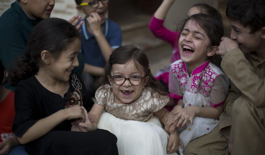 Pakistan's Maria, 6, center, who is suffering from MPS a rear genetics disorder, plays with her family members in Rawalpindi, Pakistan, Thursday, Oct. 20, 2016. Maria is just six years old but most of her young life has been spent in pain caused by a rare disease that will leave her unable to walk unless she has surgery. A U.S. hospital is willing to perform the surgery free of charge but the family has twice been refused a U.S. visa by the embassy in Islamabad and a third application has been submitted but Maria's father Shahid Ullah said Thursday he was told his application would take time. But Maria's surgery is scheduled for Nov. 2. (AP Photo/B.K. Bangash)