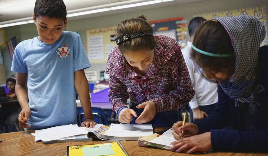 In this Tuesday, Oct. 4, 2016 photo, Abdulhamid Ashehneh, 12, works on English language exercises with fellow students in a class filled with refugee children at Cajon Valley Middle School in El Cajon, Calif. According to the U.S. State Department, nearly 80 percent of the more than 11,000 Syrian arrivals over the past year were children. Many of those children are enrolling in public schools around the country, including Chicago; Austin, Texas; New Haven, Connecticut; and El Cajon, which received 76 new Syrian students the first week of school.. (AP Photo/Christine Armario)