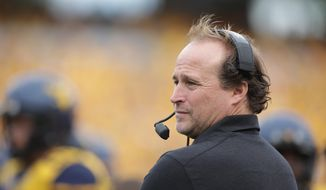 FILE - In this Sept. 26, 2015, file photo, West Virginia coach Dana Holgorsen watches his team play Maryland in an NCAA college football game in Morgantown, W.Va. Holgorsen took plenty of heat for West Virginia's struggles in its first four seasons after joining the Big 12. He's getting the bulk of the credit for the undefeated Mountaineers' hot start this season, one that could wind up saving his job. (AP Photo/Raymond Thompson, File)