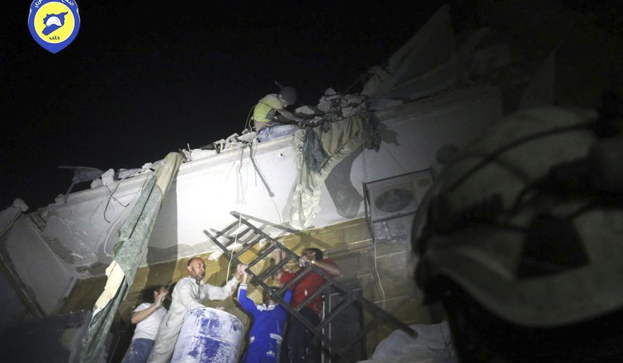 In this file photo released early Monday, Oct. 17, 2016, and provided by the Syrian Civil Defense group known as the White Helmets, rescue workers try to remove a boy stuck in the debris of a building in the neighborhood of Qaterji in rebel-held east Aleppo following an airstrike in Aleppo, Syria. The Syrian government has opened a corridor Friday, Oct. 21, 2016, for rebels and civilians who want to leave the besieged eastern neighborhoods of the city of Aleppo. (Syrian Civil Defense White Helmets via AP, File)