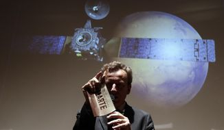 Italian Space Agency President Roberto Battiston holds a pamphlet reading in Italian 'Colonize Mars, Friday, Oct. 19, 2016, in front of a rendering showing the Schiaparelli Space Module and the planet Mars as they follow during an event organized by Italy's Space Agency, the insertion of the Trace Gas Orbiter into orbit around Mars, and the landing of the Schiaparelli module on the surface of the planet. (AP Photo/Gregorio Borgia)