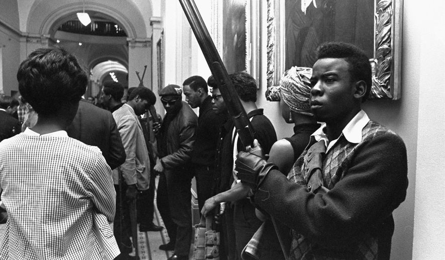 FILE - In this May 2, 1967 file photo, armed members of the Black Panthers Party stand in the corridor of the Capitol in Sacramento, Calif. Hundreds of former Black Panthers from around the world are expected to gather in Oakland, California, for a four-day conference that started Thursday, Oct. 20, 2016. The Panthers emerged from the gritty city 50 years ago, declaring a new party dedicated to defending African-Americans against police brutality and protecting their rights.  (AP Photo/Walt Zeboski, File)
