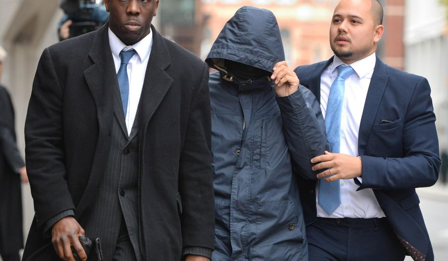"Mazher Mahmood, nicknamed the ""Fake Sheikh"" centre, arrives at the Old Bailey, London, Friday Oct. 21, 2016. A judge  Friday sentenced  British journalist Mazher Mahmood who often posed as a Middle Eastern tycoon in sting operations to 15 months in prison, after the tabloid reporter was convicted of perverting the course of justice in an effort to get scoops.  (Dominic Lipinski/PA via AP)"