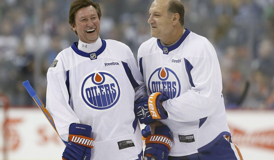 Former Edmonton Oilers hockey players Wayne Gretzky, left, and Dave Semenko joke around during a practice for the NHL's Heritage Classic Alumni game in Winnipeg, Manitoba, Friday, Oct. 21, 2016. (John Woods/The Canadian Press via AP)