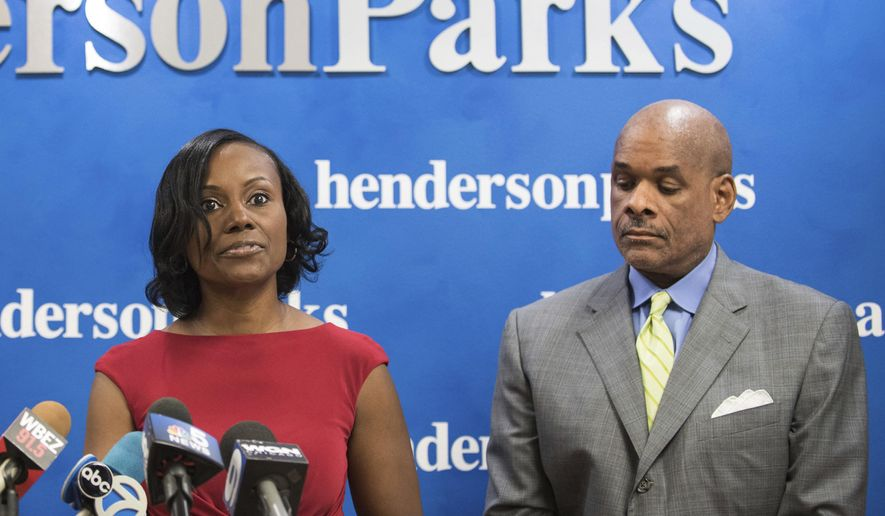 In this Sept. 22, 2016 photo, attorney Rhonda Crawford stands alongside her attorney Victor Henderson, as she addresses allegations that she impersonated a judge. Crowford, a judicial candidate, now faces charges for donning a robe and hearing real cases on the bench. The Cook County State's Attorney's Office said Friday Oct. 21, 2016 in a statement that Crawford has been indicted on charges of felony official misconduct and misdemeanor false impersonation. (Max Herman/Chicago Sun-Times via AP)