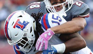 Massachusetts' Jackson Porter stops Louisiana Tech receiver Kam McKnight during the first half of an NCAA college football game Saturday, Oct. 15, 2016, in Foxborough, Mass. (Matthew J. Lee/The Boston Globe via AP)