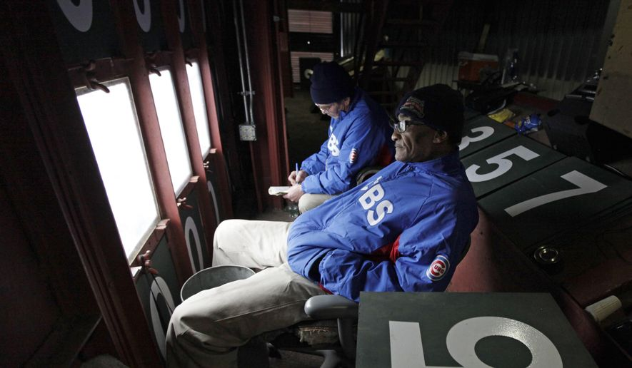 FILE - In this April 10, 2014 file photo, scoreboard operators Fred Washington, right, and Brian Helmus look out to the field from inside of the scoreboard at Wrigley Field during a baseball game between Pittsburgh Pirates and Chicago Cubs in Chicago. Fred Washington is retiring from his job as a Wrigley Field scoreboard operator, and he is hoping to finish his career in the World Series, Friday, Oct. 21, 2016. (AP Photo/Kiichiro Sato, File)
