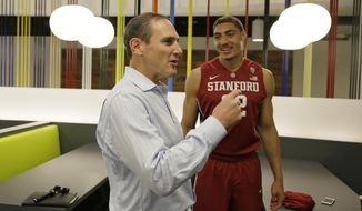 Pac-12 Commissioner Larry Scott, left, visits with Stanford forward Reid Travis, right, during NCAA college basketball Pac-12 media day Friday, Oct. 21, 2016, in San Francisco. (AP Photo/Eric Risberg)