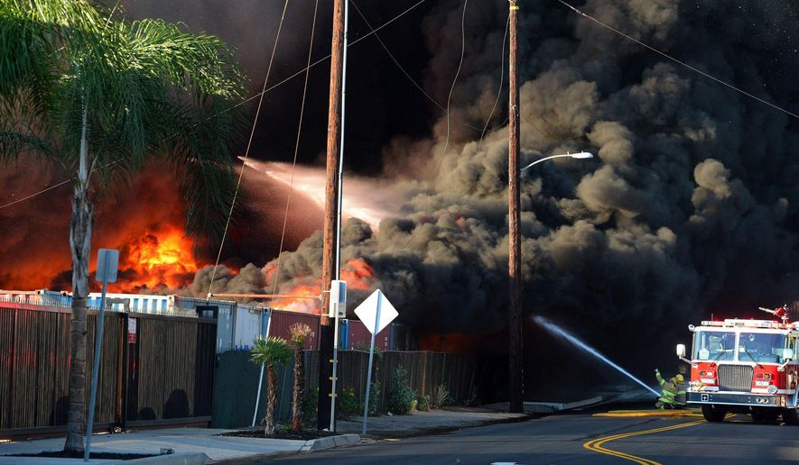 Firefighters attempt to get the handle on a fire burning at a recycling center near State Street and Bon View Avenue on the southside of the city of Ontario, Calif., Friday, Oct. 21, 2016. A fast-moving fire at a Southern California recycling center has sent huge flames into the air and a plume of smoke that can be seen for miles. The fire erupted Friday afternoon in a sprawling yard of cardboard bales and wooden pallets in Ontario, about 35 miles east of downtown Los Angeles. (Will Lester/The Inland Valley Daily Bulletin, SCNG, via AP)