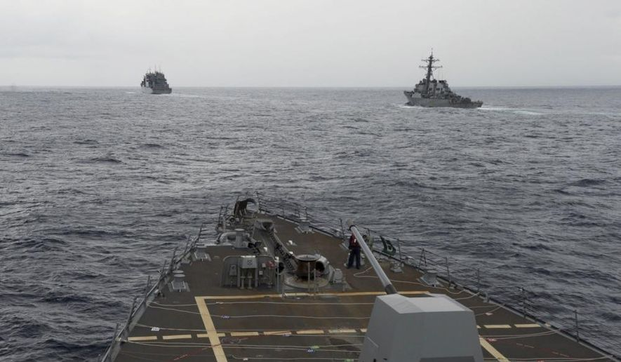 This image provided by the U.S. Navy, taken Oct. 17, 2016, shows the guided missile destroyer USS Decatur, right, pulling into position behind the Military Sealift Command USNS Matthew Perry, during a replenishment-at-sea, seen from the bridge of the guided-missile destroyer USS Spruance, in the South China Sea. The Defense Department says a U.S. Navy warship has conducted a freedom of navigation operation in the South China Sea, where China and five other countries have competing territorial claims. A department spokesman, Navy Cmdr. Gary Ross, said the destroyer ship USS Decatur conducted the transit operation Friday, Oct. 21, 2016, near the Paracel Islands. (U.S. Navy/Petty Officer 2nd Class Will Gaskill via AP)