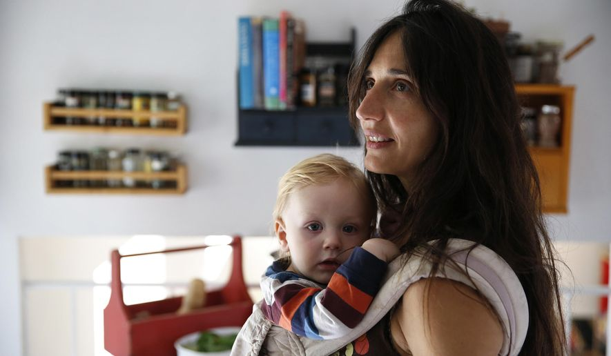 In this Oct. 20, 2016 photo, vegan mother Fulvia Serra carries her 1-year-old baby, Sebastiano, at home in Fort Collins, Colo. Serra, originally from Italy, and her husband, Scott, are raising their son vegan. Despite criticism and innuendo from some circles, pediatricians and nutritionists agree it's perfectly healthy to feed babies a vegan diet. However, parents need to be well-informed about the nutritional elements different foods offer, and work closely with their doctor or health care provider. (AP Photo/Brennan Linsley)