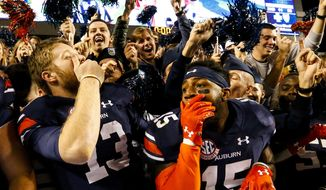 Auburn quarterback Sean White (13) and defensive back Joshua Holsey (15) celebrate after they defeated Arkansas 56-3 in an NCAA college football game, Saturday, Oct. 22, 2016, in Auburn, Ala. (AP Photo/Butch Dill) ** FILE **