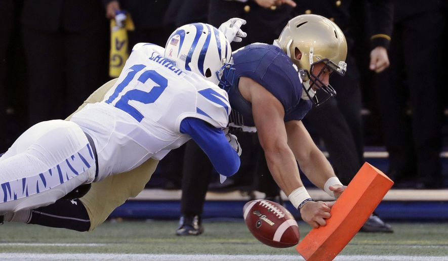 Navy quarterback Will Worth, right, loses possession of the ball as he attempts to score a touchdown against Memphis defensive back Chauncey Lanier in the first half of an NCAA college football game in Annapolis, Md., Saturday, Oct. 22, 2016. (AP Photo/Patrick Semansky)