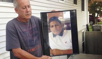 FILE- In this Sept. 27, 2016 file photo, Abraham Chaparro, holds a photograph of his murdered stepson, Miguel Garcia-Moran, outside his home in Brentwood, N.Y. Garcia-Moran is among four teenagers from Brentwood High School that have been found dead this past month in a string of brutal killings that assistant Suffolk County Police Commissioner Justin Meyers says may be tied to gang violence. (AP Photo/Claudia Torrens, File)