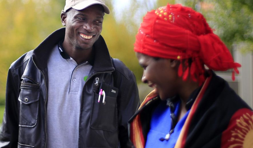 In this Tuesday, Oct. 11, 2016 photo, Gilbert Hategeka, left, and Chantal Nyiramanza share a laugh together outside the Missoula International Rescue Committee office, in Missoula, Mont. The couple and their four children were the last of five families of Congolese who arrived in Missoula in August and September. (Tommy Martino  /The Missoulian via AP)