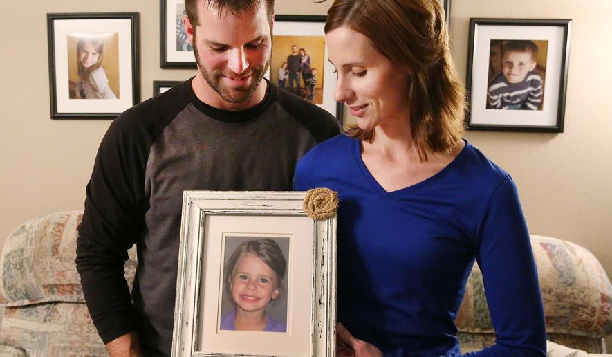 Jen and Phil Elgersma hold a picture of their daughter Autumn in their Orange City, Iowa, home Tuesday, Oct. 11, 2016. Autumn died at age 3 in 2013 from injuries inflicted by her daycare provider. Autumn is the namesake of Autumn's Center, a center providing behavioral health services for children that will open soon in Spencer, Iowa. (Jim Lee/Sioux City Journal via AP)