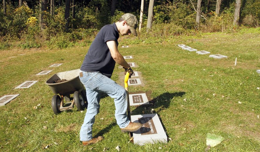 ADVANCE FOR WEEKEND EDITIONS - In this Tuesday, Oct. 11, 2016, photo, Anderson Memorials employee Cole Smith, of Rochester, installs gravestones at the Rochester State Hospital Cemetery at Quarry Hill Park in Rochester, Minn. Thanks to a decade-long grave marker project and the work of genealogists, the memory of hundreds of patients buried there is being resurrected. (Elizabeth Nida Obert/The Rochester Post-Bulletin via AP)