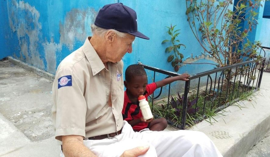 In this undated photo provided by Remote Area Medical, Remote Area Medical founder Stan Brock sits with a young Haitian boy in western Haiti, where RAM is participating in post-Hurricane Matthew relief efforts. (Eric Hutchinson/Remote Area Medical via AP)