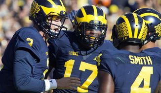 Michigan quarterback Wilton Speight, left, celebrates a touchdown with tight end Tyrone Wheatley (17) and running back De'Veon Smith (4) in the first quarter of an NCAA college football game against Illinois at Michigan Stadium in Ann Arbor, Mich., Saturday, Oct. 22, 2016. (AP Photo/Tony Ding)