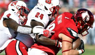 Louisville's Cole Hikutini (18) is brought down by North Carolina State's Shawn Boone (24) and Jerod Fernandez (4) during the first half of their NCAA college football game, Saturday, Oct. 22, 2016, in Louisville, Ky. (AP Photo/Timothy D. Easley)