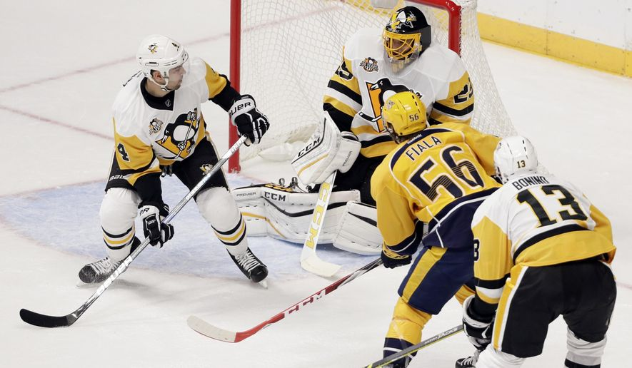 A shot by Nashville Predators left wing Kevin Fiala (56), of Switzerland, goes over the net as Pittsburgh Penguins goalie Marc-Andre Fleury (29), Justin Schultz (4) and Nick Bonino (13) defend during the first period of an NHL hockey preseason game Saturday, Oct. 22, 2016, in Nashville, Tenn. (AP Photo/Mark Humphrey)