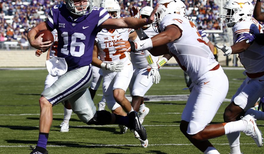 Kansas State quarterback Jesse Ertz (16) pushes aside Texas safety Jason Hall(31) as he runs for his second touchdown during an NCAA college football game, Saturday, Oct. 22, 2016, in Manhattan, Kan. (Bo Rader /The Wichita Eagle via AP)