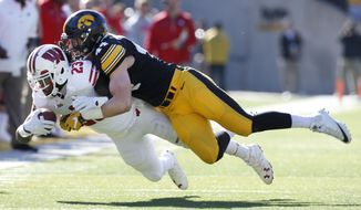 Wisconsin running back Dare Ogunbowale (23) is tackled by Iowa linebacker Ben Niemann after making a reception during the first half of an NCAA college football game, Saturday, Oct. 22, 2016, in Iowa City, Iowa. (AP Photo/Charlie Neibergall)