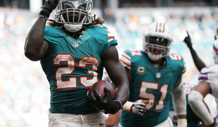 Miami Dolphins running back Jay Ajayi (23) celebrates a touchdown during the second half of an NFL football game against the Buffalo Bills, Sunday, Oct. 23, 2016, in Miami Gardens, Fla. To the right is Miami Dolphins center Mike Pouncey (51). (AP Photo/Wilfredo Lee)
