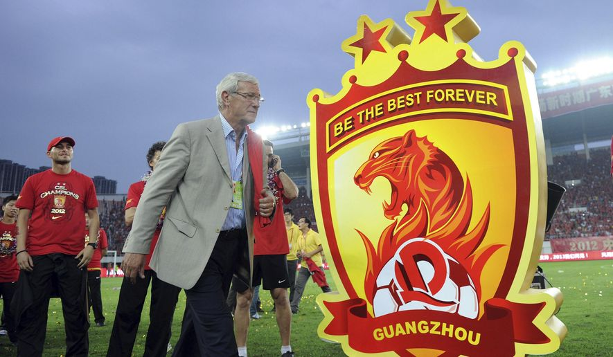 In this photo taken Oct. 27, 2012, then Guangzhou Evergrande coach Marcello Lippi walks by a sign of the club's badge after winning the championship of China's top soccer league in Guangzhou in south China's Guangdong province. Lippi was hired Saturday, Oct. 22, 2016 to take over the Chinese national football team in the latest sign of China's commitment to becoming a serious force in world soccer. (Chinatopix Via AP)
