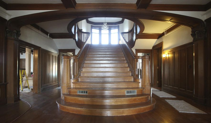 "ADVANCE FOR THE WEEKEND OF OCT. 22-23 AND THEREAFTER - An Oct. 11, 2016 photo shows the grand staircase of the original Kahl mansion in Davenport, Iowa. The staircase and main-level rooms have be restored while the second and third floors will be reconfigured into two bedroom apartments. Workers are in the final stretch of turning the original 18,000-square-foot mansion, as well as its 1960s and 1980s additions, into what developer Chris Ales calls 49 ""nice"" senior living apartments. (Kevin E. Schmidt/Quad-City Times via AP)"