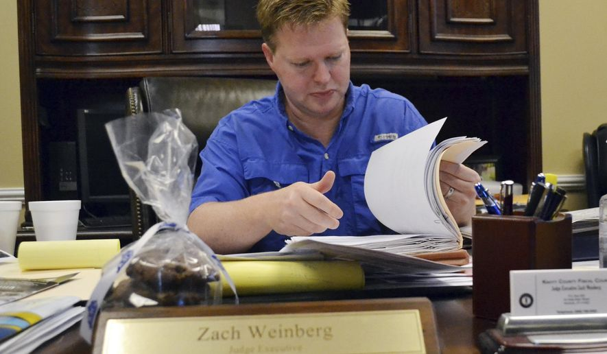 In this Aug. 31, 2016 photo, Knott County Judge executive Zach Weinberg looks through a file full of debts from a coal company owned by Jim Justice in Hindman, Ky. Justice is running as a Democrat for governor in neighboring West Virginia but his coal companies owe millions in taxes to several Kentucky counties amid a decline in coal production. (AP Photo/Dylan Lovan)