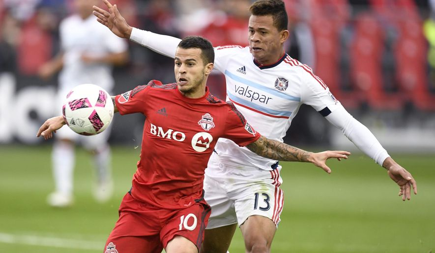 Toronto FC's Sebastian Giovinco, left, evades Chicago Fire's Rodrigo Ramos during second half MLS soccer action in Toronto, Sunday, Oct. 23, 2016. (Frank Gunn/The Canadian Press via AP)