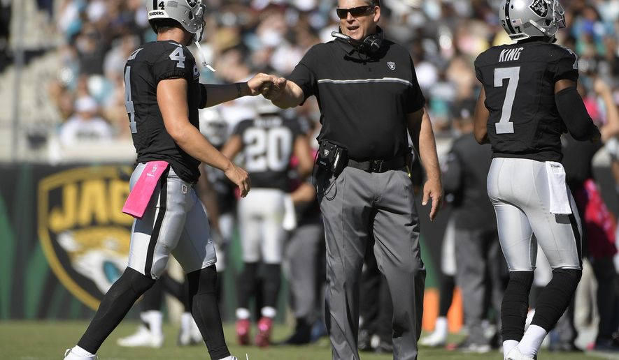 Oakland Raiders head coach Jack Del Rio celebrates with quarterback Derek Carr (4) during the third quarter of an NFL football game against the Jacksonville Jaguars Sunday, Oct. 23, 2016, in Jacksonville, Fla. (AP Photo/Phelan Ebenhack)