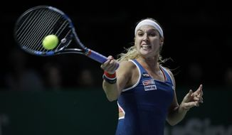 Dominika Cibulkova of Slovakia makes a forehand return to Angelique Kerber of Germany during their singles match at the WTA tennis tournament in Singapore, Sunday, Oct. 23, 2016. (AP Photo/Wong Maye-E)