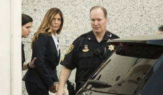 Former Pennsylvania Attorney General Kathleen Kane is escorted from Montgomery County courthouse for her scheduled sentencing hearing in Norristown, Pa, Monday, Oct. 24, 2016. Kane was sentenced Monday to 10 to 23 months in jail for illegally disclosing details from a grand jury investigation to embarrass a rival and lying about it under oath. (AP Photo/Matt Rourke)
