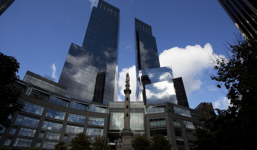 A statue of Christopher Columbus stands between the towers of the Time Warner building, Monday, Oct. 24, 2016, in New York. AT&T plans to buy Time Warner for $85.4 billion. (AP Photo/Mark Lennihan)