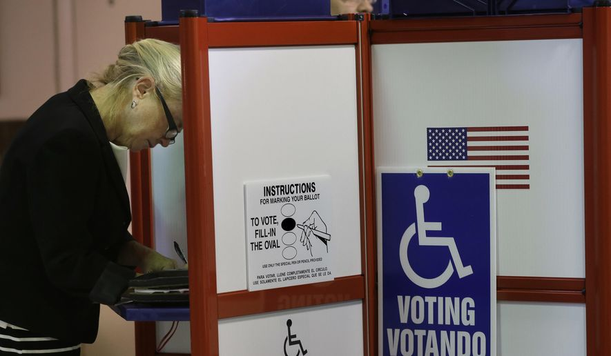 Voter Marla Pyle, of Worcester, Mass., left, fills out a ballot at an early voting location, Monday, Oct. 24, 2016, in Worcester, Mass. For the first time in Massachusetts, voters can cast their ballots for president before Election Day. Early voting begins Monday and will continue through Nov. 4. (AP Photo/Steven Senne)